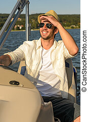 Young man navigating powerboat sunny - Man in sunglasses and...