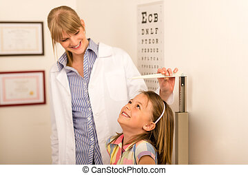 Pediatrician measure height of little girl at medical office
