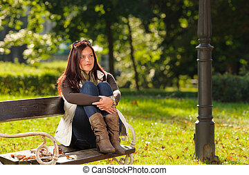Autumn sunset park woman sitting on bench