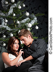 Extravagant man and woman in front of Christmas tree and...