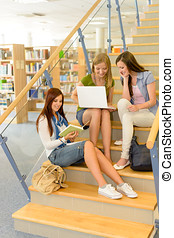 Group of high school classmates study library - Three...