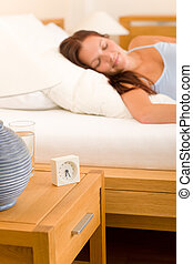 Alarm clock Woman sleeping in white bed