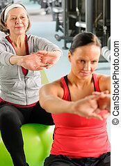Two women at gym stretch out - Senior woman with personal...