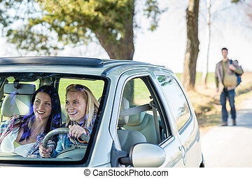 Exciting girls drive car taking hitch-hiker - Two women...