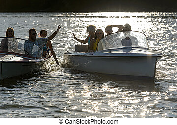 Silhouette of young friends in motorboats - Silhouette of...