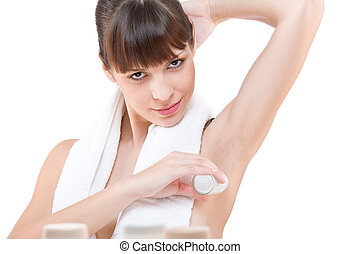 Body care: Young woman applying deodorant on white...