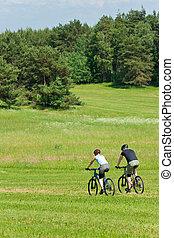 Sport mountain couple biking downhill sunny meadows - Sport...