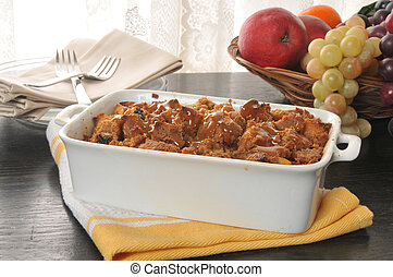 Bread pudding with caramel butterscotch sauce in a baking...