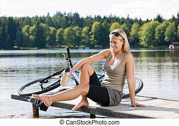 Sport biking young woman sitting by lake - Sport biking...