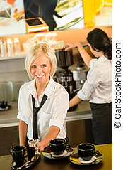 Waitress serving coffee cups making espresso woman cafe bar...