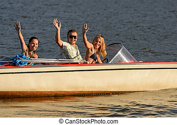 Young people waving from motorboat enjoying summer break