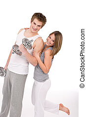 Fitness - Smiling healthy couple exercising with weights on...