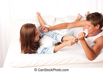 Young woman and man having fun in bed and fighting togehter...