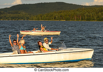 Group of friends racing with motorboats - Group of cheerful...