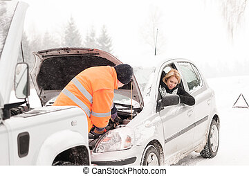 Man repairing womans car snow assistance winter broken tools...