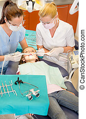 Dentist with nurse doing procedure on child - Dentist and...