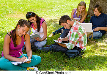 Students sitting in park studying reading writing