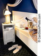 Romantic empty bed intimate moment slippers champagne hotel...