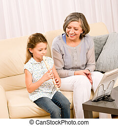 Grandmother teach young girl play flute happy - Grandmother...