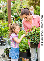 Mother daughter choosing flowers in garden shop - Mother and...