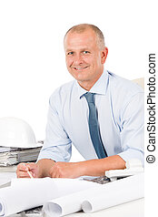 Professional architect with blueprint behind table -...