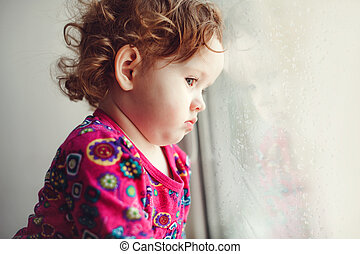 Sad little girl looking out the window