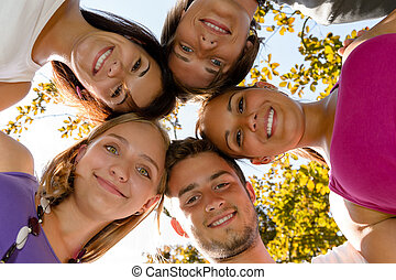 Teens in a circle smiling in park leisure students friends