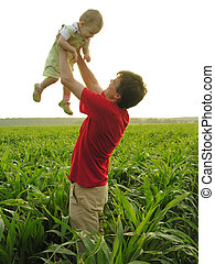 father with baby in field