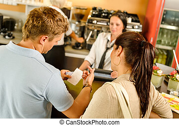 Man checking receipt at cafe payment - Man checking receipt...