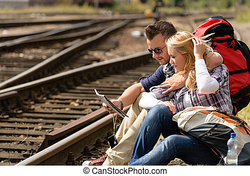Couple looking at map sitting on railroad