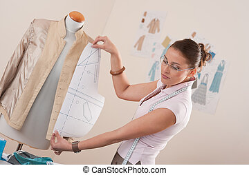 Female fashion designer working with pattern cutting at...