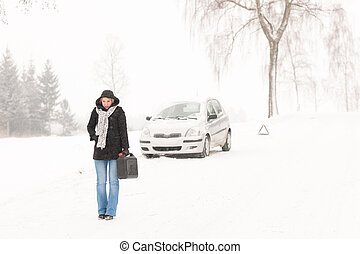 Woman walking with gas can winter car