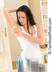 Woman applying roll-on deodorant in bathroom - Young...