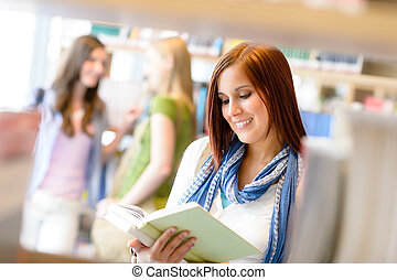 Teenage woman read among book shelves library - Teenage...