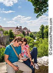 Young couple on vacation looking at map