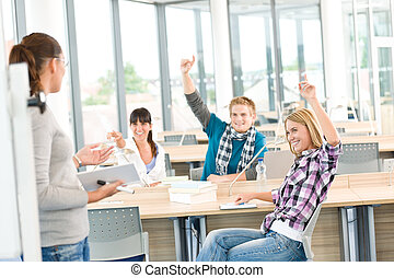 High school students raising hands, in classroom with...