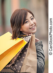 Happy smiling shopping woman holding bags in the street.