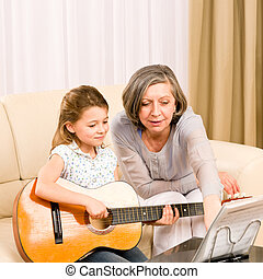 Young girl sing play guitar to grandmother - Young girl...