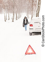 Woman walking with gas can car snow