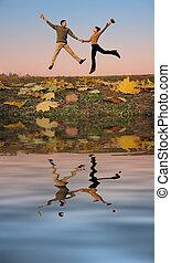 jump couple. autumn leaves. sunset water