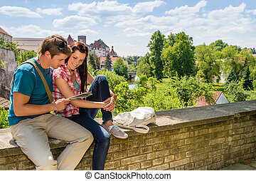Young couple on vacation looking at map - Young happy couple...