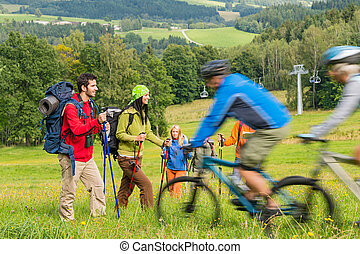Tourists hiking and riding mountain bikes summer nature -...