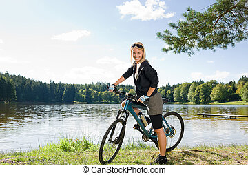 Mountain biking young woman relax by lake - Beautiful young...