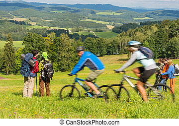 People hiking, riding bicycles on springtime weekend - Young...