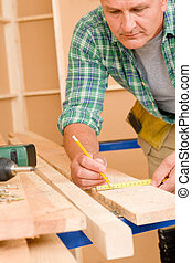Handyman home improvement close-up of measure wooden board...