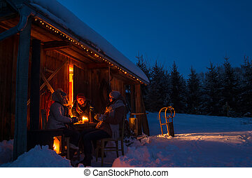 Evening winter cottage friends enjoy hot drinks in snow...