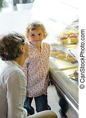 Woman with child girl choose cake bakery