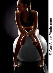 Young sporty woman relaxing on fitness ball on black...