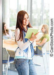 Young student girl reading book at high-school - Female...