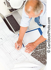 Senior man work on blueprints construction plans - Closeup...
